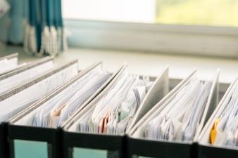 Wiersz dokumentów białego papieru w czarnym folderze na stole biura roboczego, pliki raportu