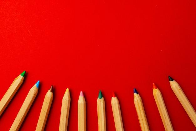 Wiersz kolorów drewniane ołówki na czerwonym tle widok z góry
