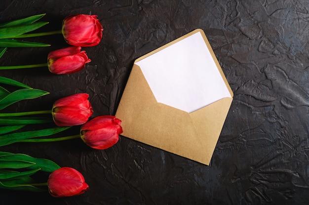 Wiersz kwiatów tulipanów z kopertą na czarnym tle z teksturą, miejsce widok z góry