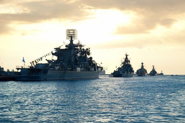 Wiersz okrętów wojskowych przed morskim zachodem słońca