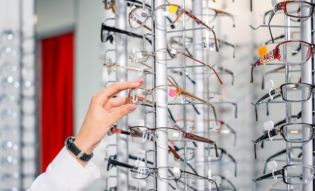 Wiersz okularów u optyka. sklep z okularami. stań z okularami w sklepie z optyką. prezentacja z okularami w nowoczesnym sklepie okulistycznym. zbliżenie.