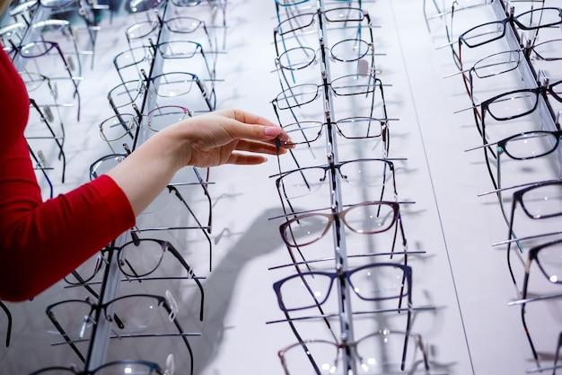 Wiersz okularów u optyka. sklep z okularami. stań z okularami w sklepie z optyką. ręka kobiety pokazuje okulary. przedstawianie spektakli. zbliżenie