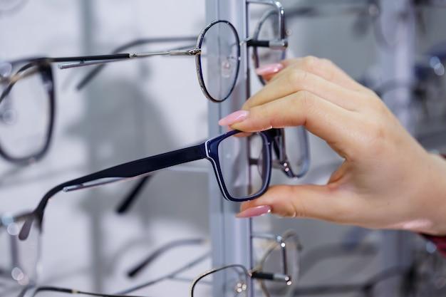 Wiersz okularów u optyka. sklep z okularami. stań z okularami w sklepie z optyką. ręka kobiety pokazuje okulary