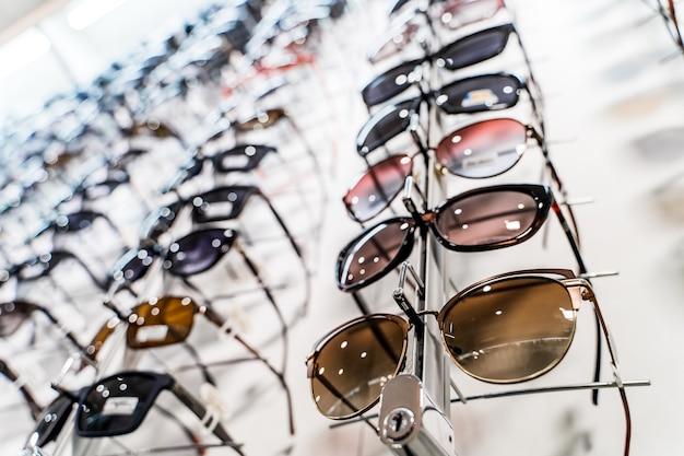 Wiersz okularów u optyka. sklep z okularami. stań z okularami w sklepie z optyką. surowe modne okulary przeciwsłoneczne w sklepie.