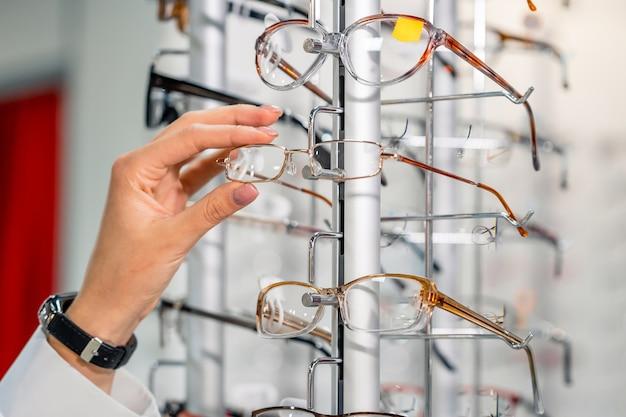 Wiersz okularów u optyka. sklep z okularami. stojak z okularami w sklepie z optyką. prezentacja z okularami w nowoczesnym sklepie okulistycznym. ręcznie dobierając okulary. zbliżenie.