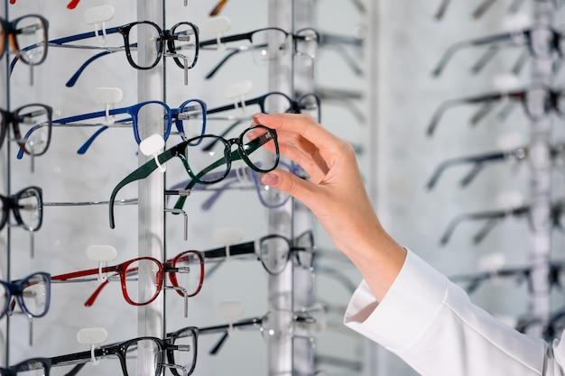 Wiersz okularów u optyka. sklep z okularami. stojak z okularami w sklepie z optyką. ręka kobiety wybiera okulary