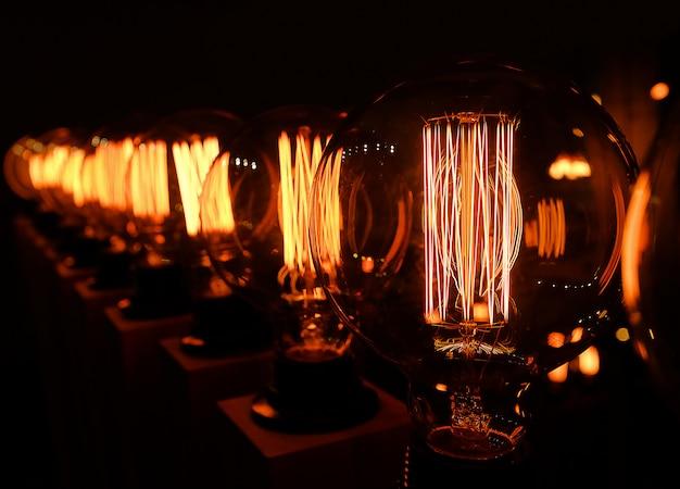 Wiersz retro lampy edison szkło na ciemnym tle, makro. projektant światła i oświetlenia we wnętrzach. selektywne ustawianie ostrości.