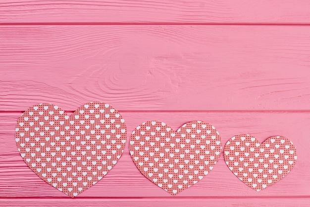 Wiersz serc papieru na różowym tle drewnianych.