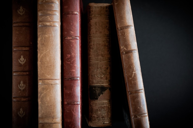 Wiersz starych książek na białym tle na czarnym tle