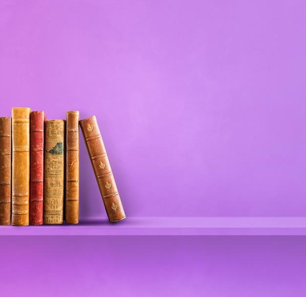 Wiersz starych książek na fioletowej półce. kwadratowe tło sceny