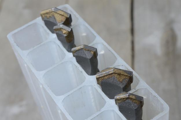 Wiertła z wiertłami udarowymi z węglików spiekanych leżą w plastikowej walizce na drewnianej desce. zbliżenie.
