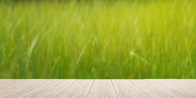 Wierzchołek drewnianej deski lub tarasu z rozmytym widokiem na pole ryżu. miękki stonowany kolor.