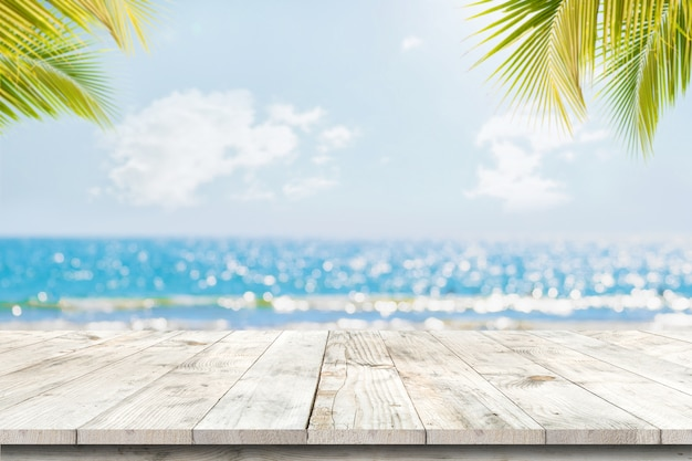 Wierzchołek drewno stół z seascape i palma liśćmi, plamy bokeh światło spokojny morze i niebo przy tropikalną plażą