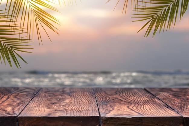 Wierzchołek stół z drewna na niewyraźne morze na zachód słońca z tłem drzewa kokosowego. pusty gotowy do montażu wyświetlacza produktu. koncepcja plaży latem.