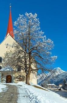 Wieś haselgehr i katolicki kościół parafialny św. marcina. zimowy widok (austria, tyrol). 1689 nazwano kaplicę w martin unterhof. 1704 miała miejsce nowa budowla.