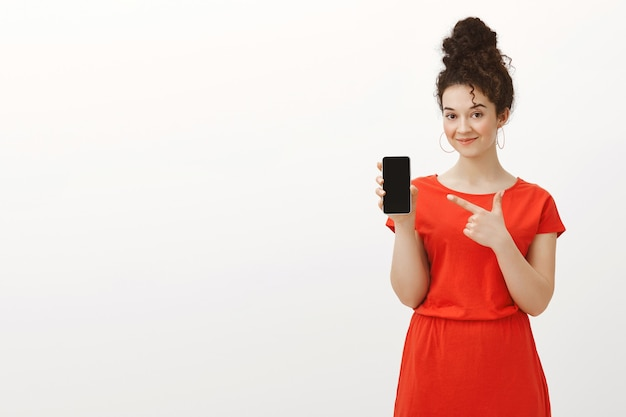 Wiesz, jaki gadżet kupić dalej. portret zalotnej przystojnej koleżanki w stylowej czerwonej sukience z kręconymi włosami uczesanymi w kok