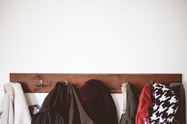 Wieszak drewniany pełen płaszczy na białej ścianie