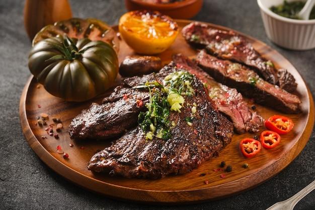 Wieszak grillowy stek z sosem chimichurri na drewnianym talerzu, z bliska.