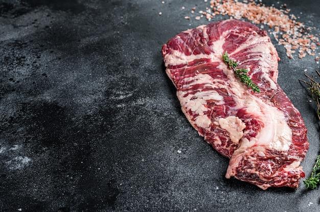 Wieszak lub stek z surowego mięsa wołowego wołowego na stole rzeźnika z ziołami
