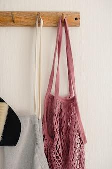 Wieszak na haczyk z różową eko torbą, szarym fartuchem i czarną miotłą i szufelką zawieszony na białej ścianie w nowoczesnej kuchni. pomysły na przechowywanie.