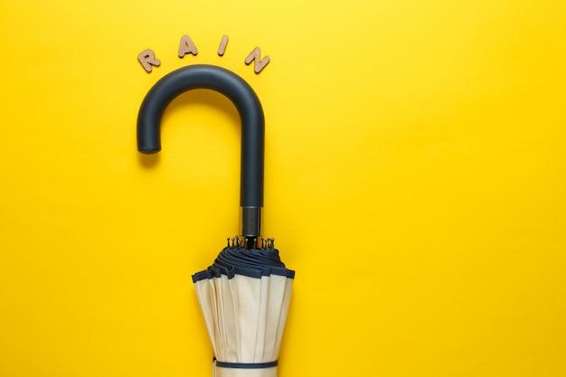 Wieszak na parasol z napisem deszcz z drewnianych liter na żółtej powierzchni.