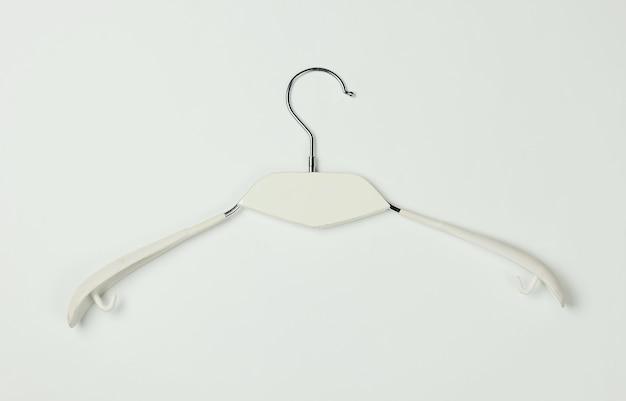 Wieszak na ubrania na białym tle. minimalistyczna koncepcja mody. strzał studio. widok z góry