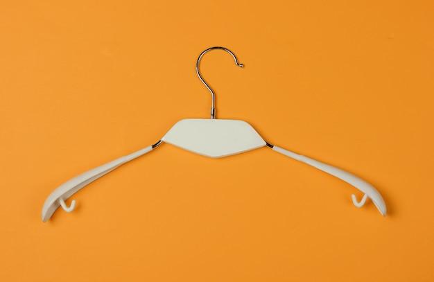 Wieszak na ubrania na żółtym tle. minimalistyczna koncepcja mody. strzał studio. widok z góry