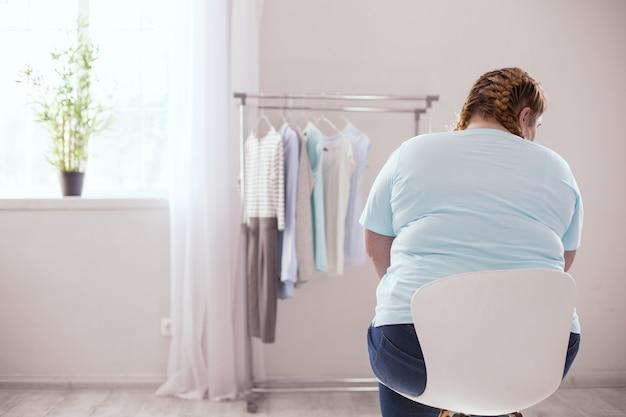 Wieszak na ubrania. tęga młoda kobieta czuje się zawiedziona, patrząc na wieszak z ubraniami