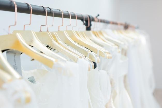 Wieszak na ubrania z sukniami ślubnymi na złotych wieszakach w rzędzie, koncepcja salonu weselnego