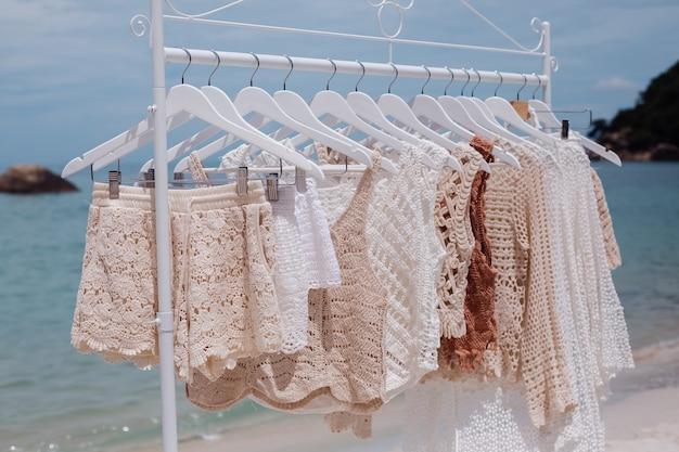 Wieszak podłogowy ze stylowymi ubraniami z dzianiny na tropikalnej plaży