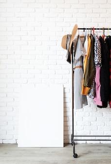 Wieszak z kolorowymi ubraniami na wieszakach na białym murem
