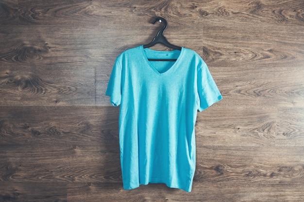Wieszak z niebieską koszulką na drewnianej ścianie