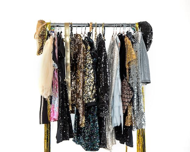 Wieszak z wieszakiem na ubrania z eleganckimi pięknymi wakacyjnymi sukienkami dla kobiet z dżetów i cekinów. przygotowanie do wydarzenia, publiczny koncert