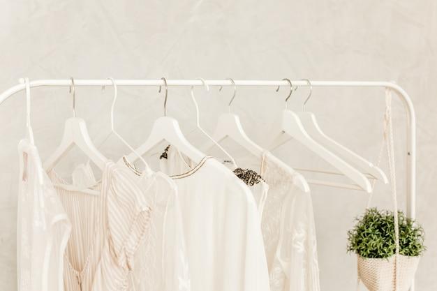 Wieszak ze stylowymi, damskimi ubraniami na jasnym tle