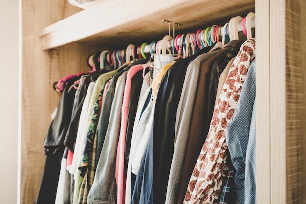 Wieszaki z różnymi ubraniami w szafie na ubrania