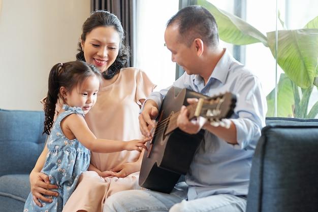 Wietnamczyk śpiewa i gra na gitarze dla swojej córeczki i żony