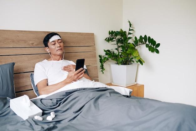 Wietnamczyk z chłodzącym żelem na czole skarży się na ból w klatce piersiowej, gdy wideo dzwoni do swojego lekarza