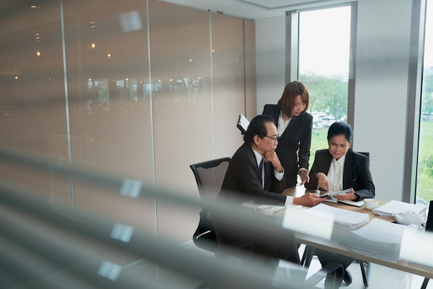 Wietnamska biznes drużyna dyskutuje dokument na pastylka komputerze