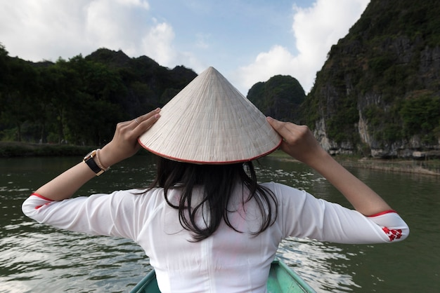 Wietnamska dziewczyna w białym kapeluszu siedzi na łodzi