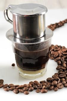 Wietnamska kawa z mlekiem skondensowanym w szklanych filiżankach i tradycyjny metalowy ekspres do kawy phin. tradycyjna metoda przyrządzania wietnamskiego wlewu do kawy. miejsce na tekst lub reklamę