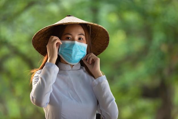 Wietnamska kobieta nosi maski, ao dai jest znanym tradycyjnym kostiumem noszącym maski, koncepcja zapobiega rozprzestrzenianiu się wirusa coronavirus 19