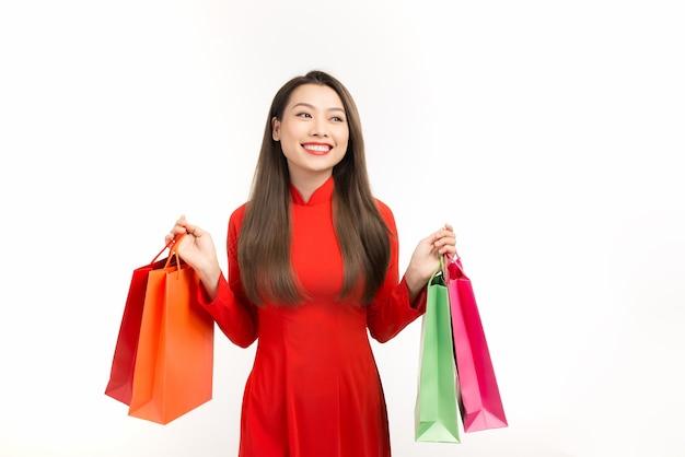 Wietnamska kobieta ubrana w tradycyjne stroje ao dai i trzymająca torby z zakupami podczas księżycowego festiwalu noworocznego