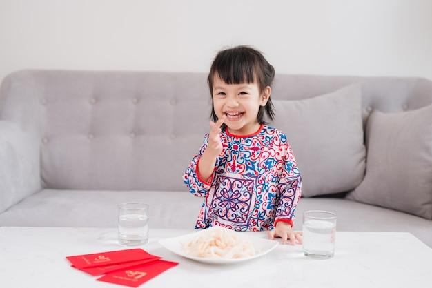 Wietnamska mała dziewczynka w tradycyjnym stroju ao dai, świętuje nowy rok w domu. tet wakacje.