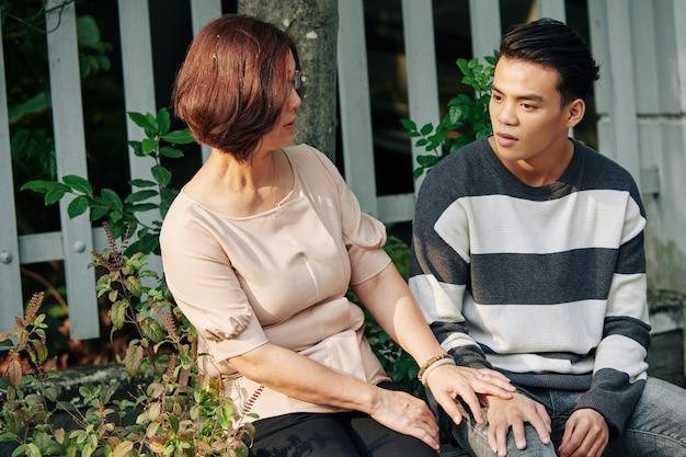 Wietnamska mama i syn siedzą na ławce przed domem i rozmawiają o nowościach i problemach