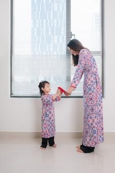 Wietnamska matka i córka w tradycyjnym stroju ao dai, świętują nowy rok w domu. tet wakacje.