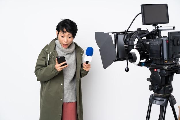 Wietnamska reporterka trzymająca mikrofon i informująca o wiadomościach zaskoczona i wysyłająca wiadomość