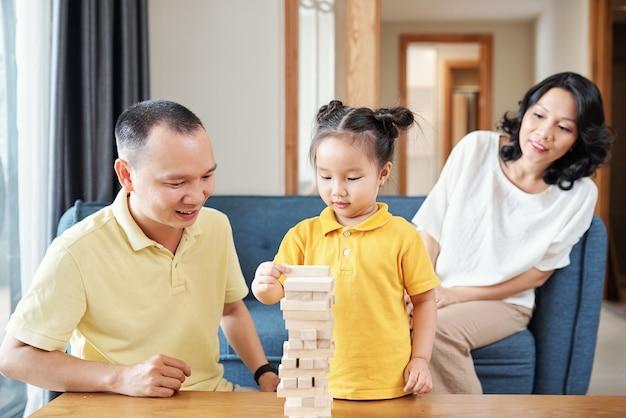 Wietnamska rodzina spędza razem czas w domu i buduje wieżę z drewnianych klocków