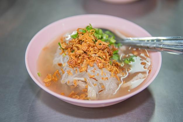 Wietnamska zupa makaron ryżowy z żeberkami wieprzowymi w widelcu i kiełbasą po wietnamsku, smażoną w głębokim tłuszczu czerwoną cebulą i pietruszką