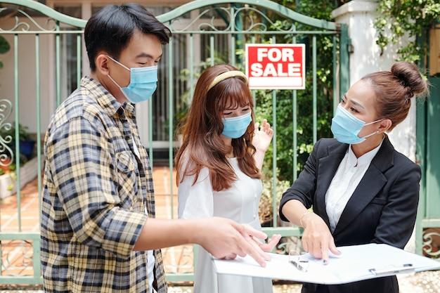 Wietnamski agent nieruchomości ral w masce medycznej pokazujący młodym klientom dokumenty z układem domu podczas spotkania