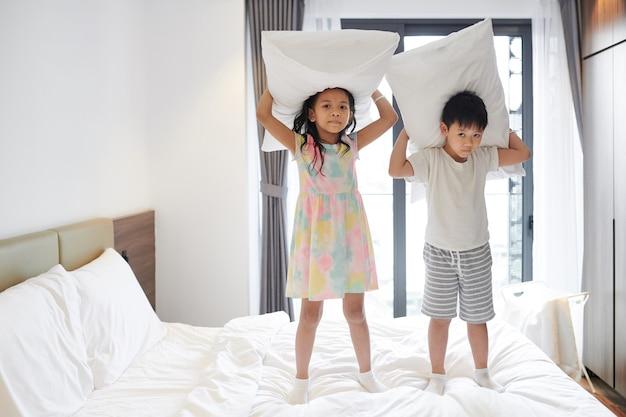 Wietnamski brat i siostra bawią się poduszkami na łóżku w sypialni rodziców i patrzą na kamerę